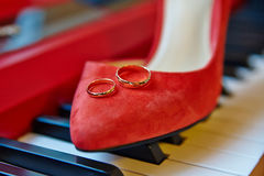 Wedding rings, bridal shoes piano keys background Royalty Free Stock Photos