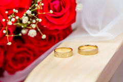 Wedding rings of bride and groom. Jewish wedding - Wedding rings of bride and groom near a bouquet of red roses. Close-up Royalty Free Stock Photos