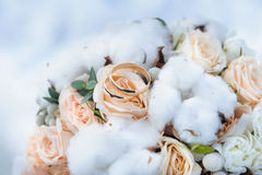 Wedding rings on the bride`s bouquet. Wedding rings on beautiful elegant wedding bouquet of roses and cotton. Winter wedding bouquet. Beautiful gold wedding Stock Photos