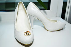 Wedding day. Wedding rings on bride`s shoes Stock Photography