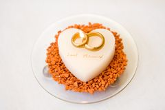 Wedding rings on cake. Overhead view of two wedding rings on love heart shaped cake with candles; white studio background Royalty Free Stock Image