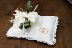 Wedding rings with calla bouquet on bridal pillow Royalty Free Stock Images