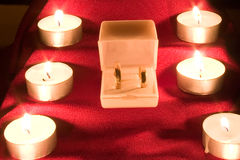 Wedding rings and candle Stock Photography