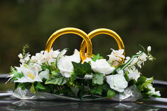 Wedding rings on the car with bunch of flowers Royalty Free Stock Images