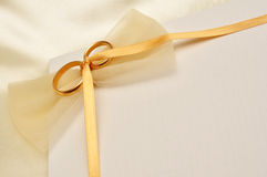 Wedding rings card. Wedding invitation card with gold rings and delicate ribbon Royalty Free Stock Image