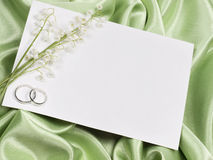 Wedding rings, card  and lily of the valley Stock Photo