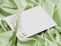 Wedding rings, card  and lily of the valley Royalty Free Stock Images