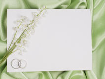 Wedding rings, card  and lily of the valley. Silver wedding rings, card  and lily of the valley green  background Stock Photo
