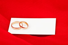 Wedding rings with card on red fabric Stock Photo