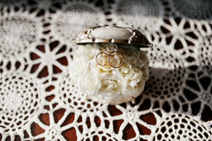 Wedding rings on casket of jewels with small rosses inside. Stock Photos