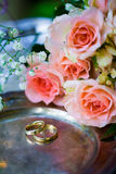 Wedding rings before the ceremony, with decorated Champagne glasses and roses. Wedding rings before the ceremony with decorated Champagne glasses and roses Stock Image