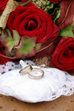 Wedding rings on chair with flowers. Still-life with wedding rings and red roses on wooden chair Royalty Free Stock Images