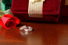 Wedding rings with Christmas gifts and a rose. Resting on a table Royalty Free Stock Image