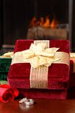Wedding rings with Christmas gifts and a rose in front of a fire. Wedding rings with Christmas gifts and a rose on a table in front of a fireplace stock image