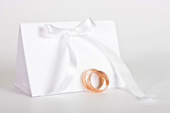 Wedding rings and complimentary ticket. Two gold wedding rings and empty complimentary ticket. High key Stock Image