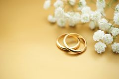 Wedding rings with copy space. Gold wedding rings on golden background with small flowers Studio shot Royalty Free Stock Images
