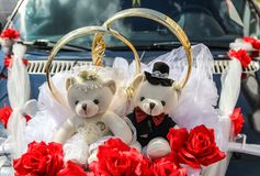 Wedding rings and couple of teddy bears on car decoration. Royalty Free Stock Photos