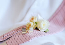 Wedding rings, cufflinks tie on the couch Royalty Free Stock Photos