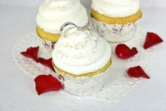Wedding rings in cupcake frosting Stock Photography