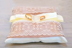 Wedding rings on a cushion. Gold wedding rings on a beige openwork cushion Royalty Free Stock Photography