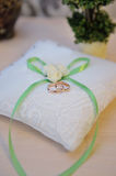 Wedding rings on a cushion with green bow Royalty Free Stock Photos