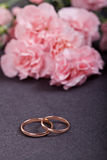Wedding rings. On dark background against pink carnations Royalty Free Stock Photography