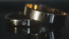 Wedding rings on dark background. Two wedding rings lie on the table on a dark background, one diamond ring, close-up stock footage