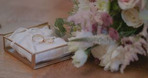 Wedding Rings in Decorated Box with flowe background. Shoot of two wedding rings in a box on table stock video