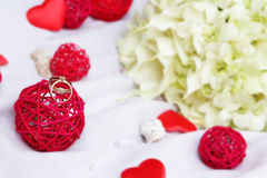Wedding rings, decoration and bridal bouquet over white Stock Image