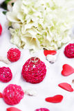 Wedding rings, decoration and bridal bouquet over white Royalty Free Stock Photography