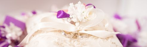 Wedding rings on a decorative cushion. With purple decorative ribbons royalty free stock images