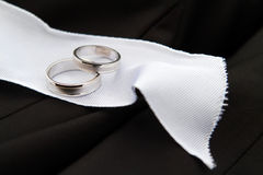 Wedding Rings detail. With wedding jacket and white ribbon Stock Images