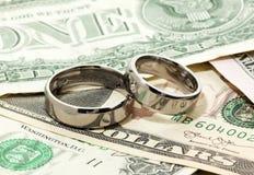 Wedding rings on dollar bills Stock Photos