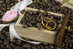 Wedding rings in a drawer. Filled with coffee beans and flower Stock Images