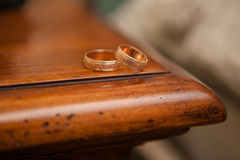 Wedding rings. On the edge of a wooden table Royalty Free Stock Photography