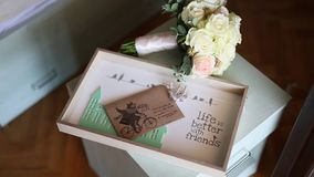 Wedding rings on an envelope with a letter with a wedding bouque. T the bride on a background stock video