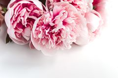 Wedding rings, envelope, peonies flowers on white background, copy space. Wedding invitation concept - rings, envelope, pink peonies flowers on white background royalty free stock images