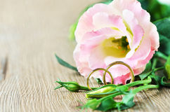 Wedding rings. And Eustoma flower on wooden background Stock Photography