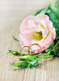 Wedding rings. And Eustoma on wooden background Royalty Free Stock Photos