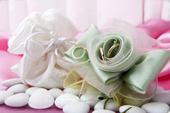 Wedding rings and  favors on elegant  fabric Stock Photography