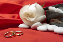 Wedding rings and  favors on elegant  fabric Royalty Free Stock Photos