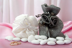 Wedding rings and  favors on elegant  fabric Stock Images
