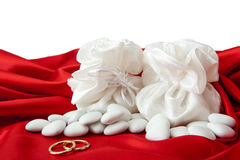 Wedding rings and  favors on elegant  fabric Stock Image
