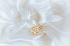 Wedding rings and figurines of doves. On white silk Royalty Free Stock Image