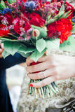 Wedding rings on finger of bride and flowers. Royalty Free Stock Photography