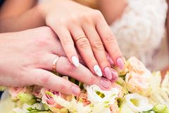 Wedding rings on fingers of young wife and husband symbolize marriage. Hands are together on the brides bouquet of roses. Beautiful wedding manicure. Golden royalty free stock photography