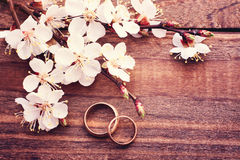 Wedding rings. Flowering branch flowers on wooden surface. Stock Photo