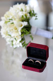 Wedding rings and flowers. Wedding rings in the nice box and the nice bouquet of flowers Royalty Free Stock Images