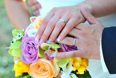 Wedding rings with flowers. Golden wedding rings on bride and groom fingers with flowers Stock Photography