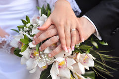Wedding rings with flowers. Wedding rings on fingers with brie bouquet Royalty Free Stock Photos